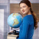 Happy female student standing on school corridor, holding globe, looking back over shoulder, smiling.http://members.upclive.hu/nyulaszi.dora/lightbox/modelNikol.jpg